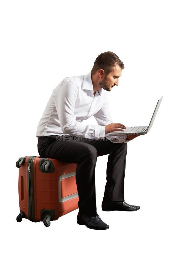 供以人员坐手提箱和看他的膝上型计算机 图库摄影