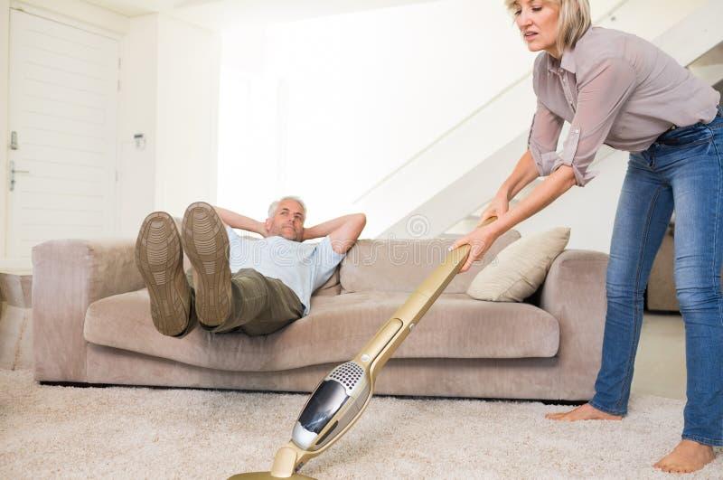 供以人员基于长沙发,当妇女吸尘的地毯时 库存照片
