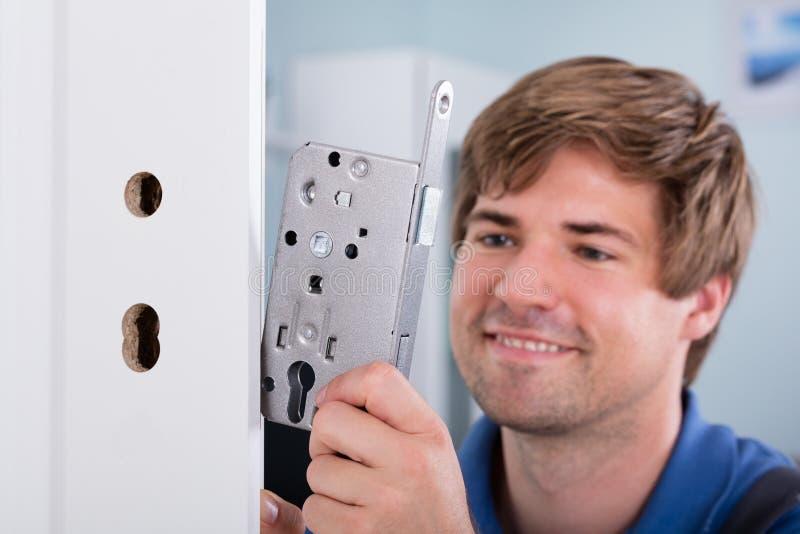 供以人员安装门锁的` s手在门 免版税库存照片