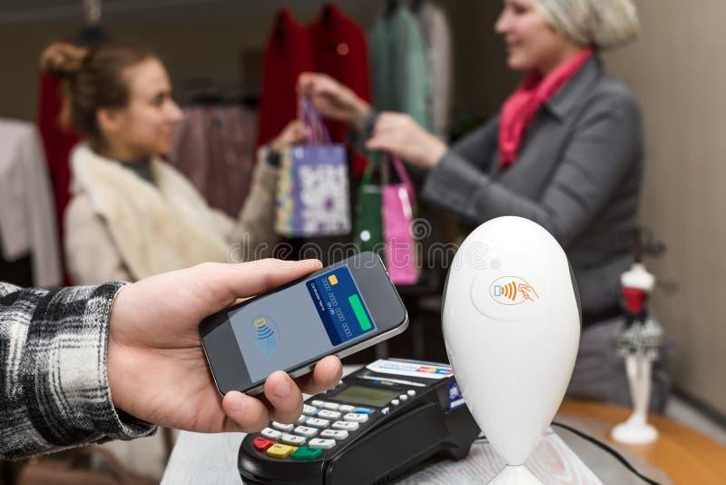 供以人员完成流动付款在商店有终端的收银处 图库摄影