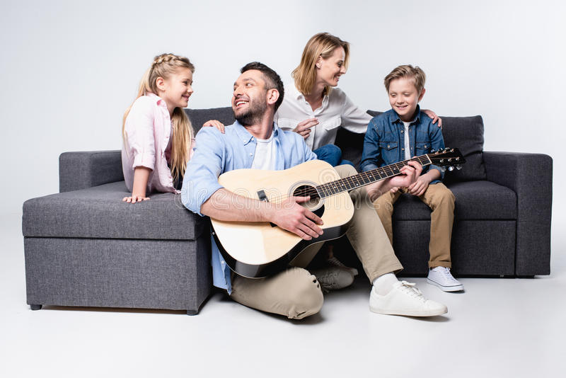 供以人员弹有家庭的声学吉他坐沙发近