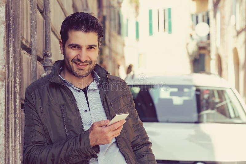 供以人员微笑拿着站立户外在他的汽车旁边的一个手机 库存图片