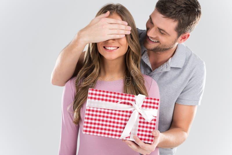 供以人员惊奇他的有礼物的女朋友在灰色背景 库存图片