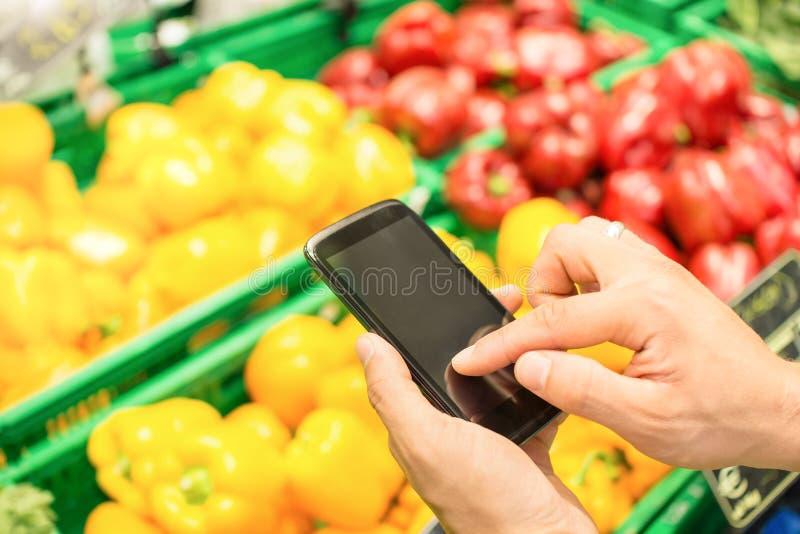 供以人员手digiting在流动巧妙的电话的-网上购物概念 免版税库存图片
