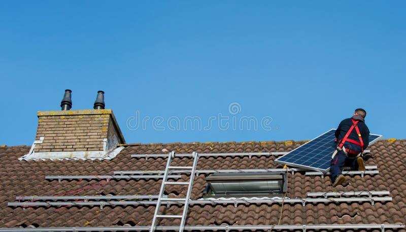 供以人员把太阳电池板放在屋顶上 免版税库存图片