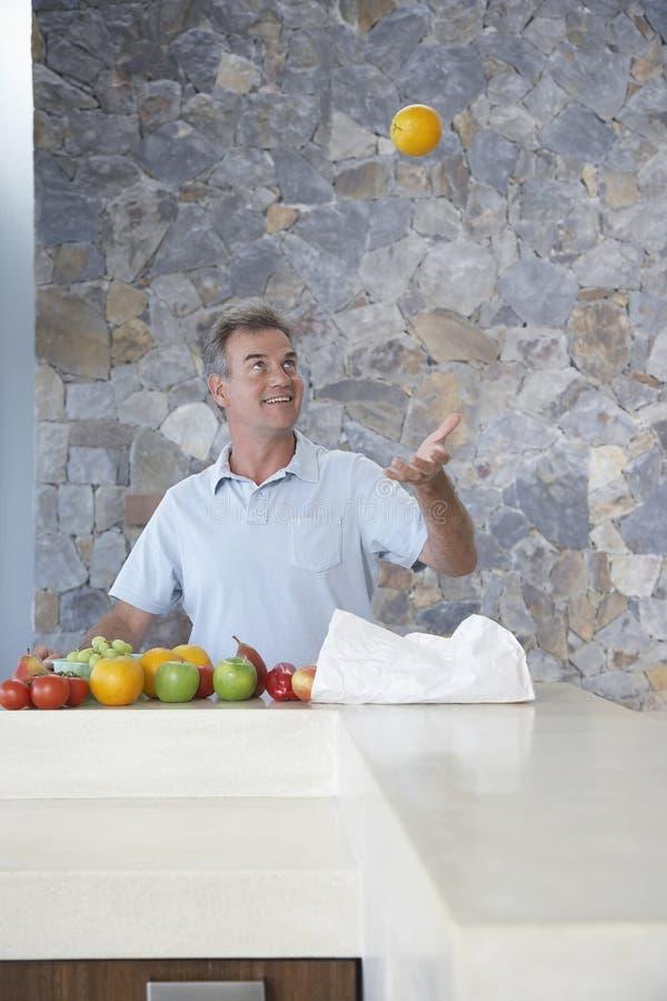 供以人员投掷的桔子入空气在厨台 免版税库存照片