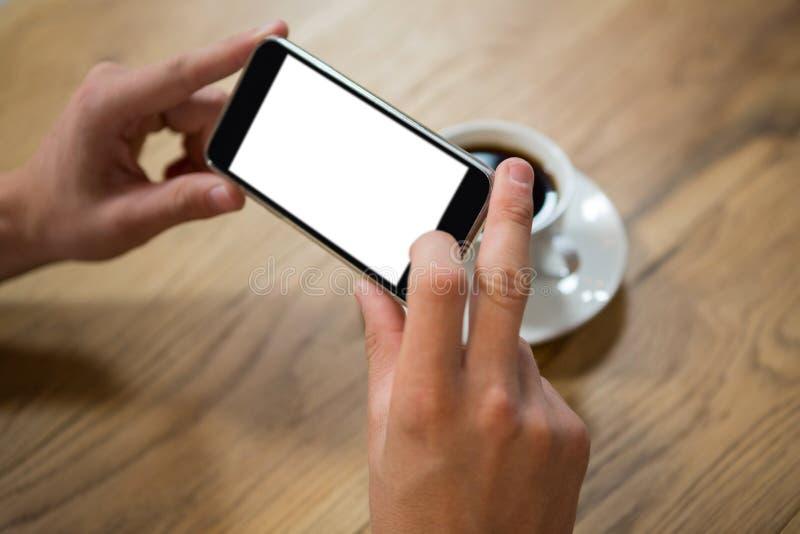 供以人员拍摄咖啡的手通过在咖啡馆的智能手机 免版税图库摄影