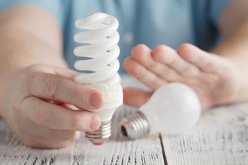 供以人员拿着一盏节能灯并且拒绝正常电灯泡 免版税库存照片