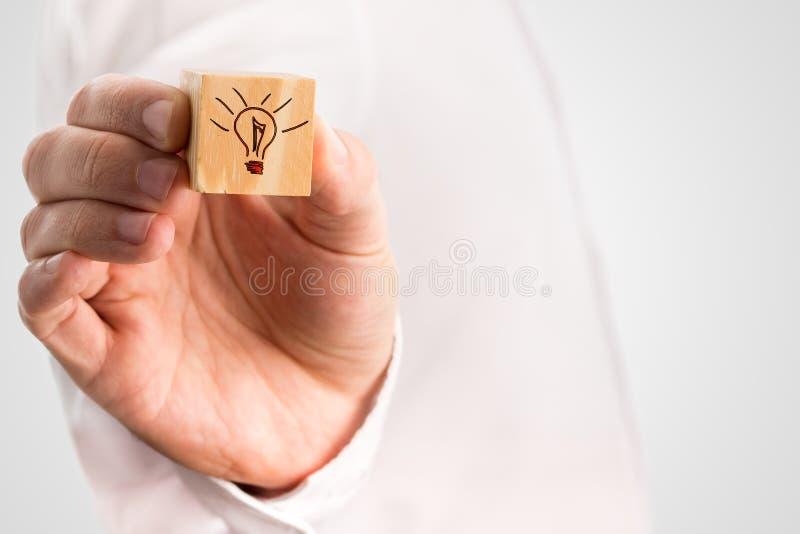 供以人员拿着与一个手拉的电灯泡的一个立方体 免版税库存图片
