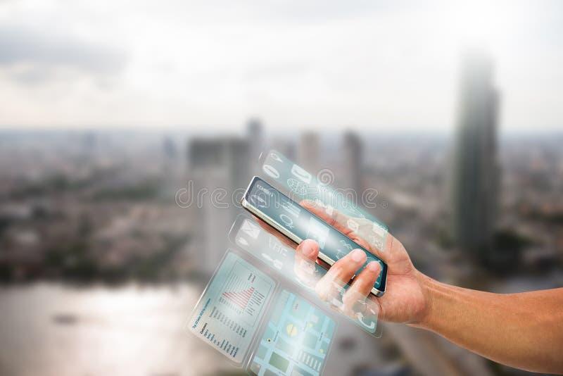 供以人员拿着有透明多屏幕的` s手智能手机在被弄脏的城市背景 库存图片