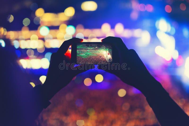 供以人员拿着电话和记录音乐会,拍照片和享受音乐节党 库存照片