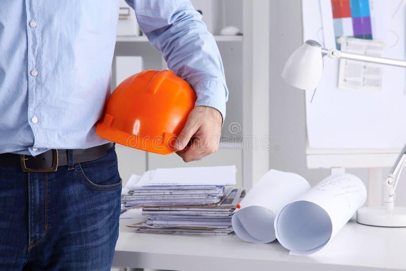 供以人员拿着盔甲的建筑师佩带的衣服,站立在办公室 库存照片