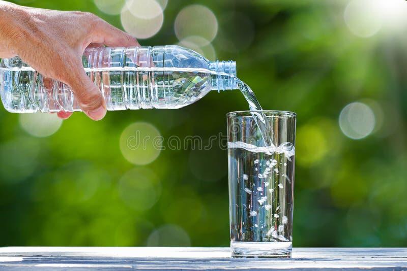 供以人员拿着饮用的瓶装水和倾吐水的` s手入在木桌上的玻璃在被弄脏的绿色自然背景 库存图片