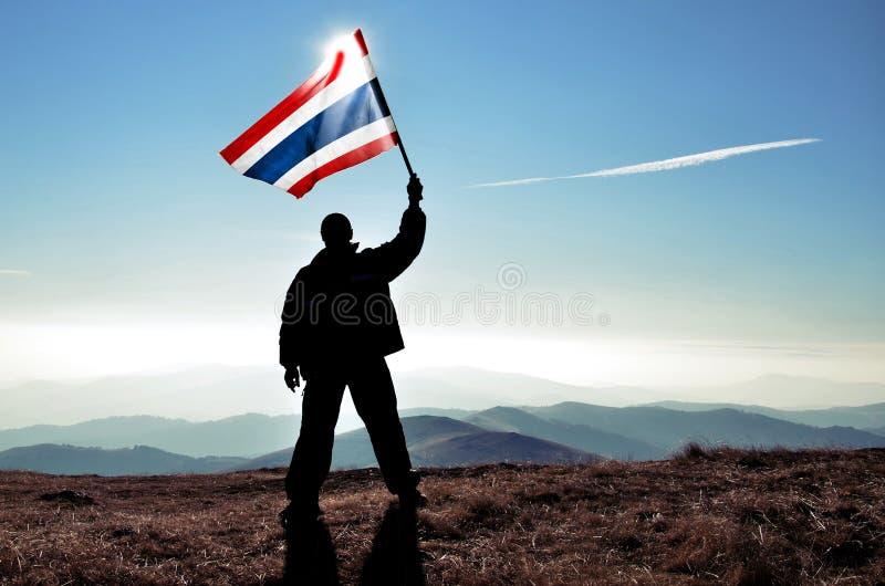 供以人员挥动泰国旗子的优胜者在山峰顶部 免版税图库摄影