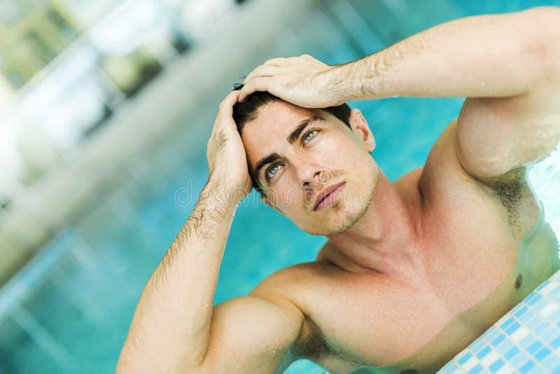 供以人员接触他的在游泳池的头发 库存图片