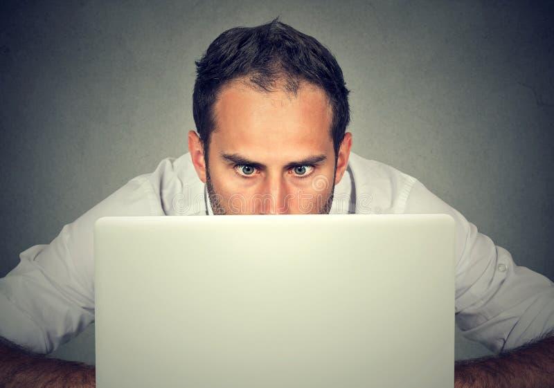 供以人员掩藏在凝视有一个震惊面孔表示的屏幕的膝上型计算机后 免版税库存照片