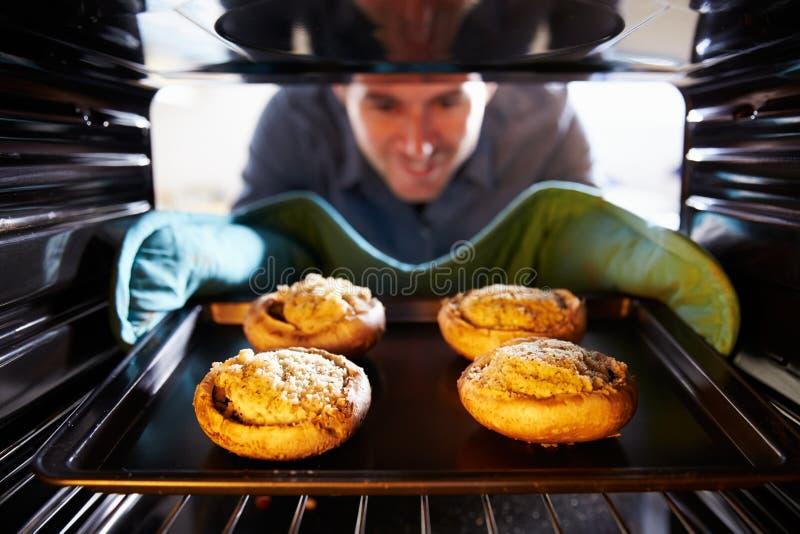 供以人员放酿蘑菇入烤箱对厨师 免版税库存图片