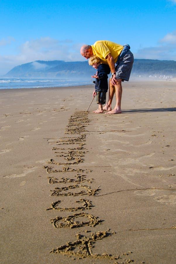 供以人员教的字母表给小男孩在海滩 图库摄影