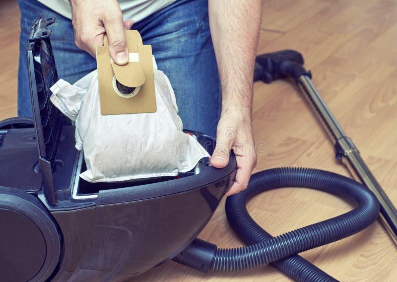供以人员替换在吸尘器的一个抖粉袋 库存照片