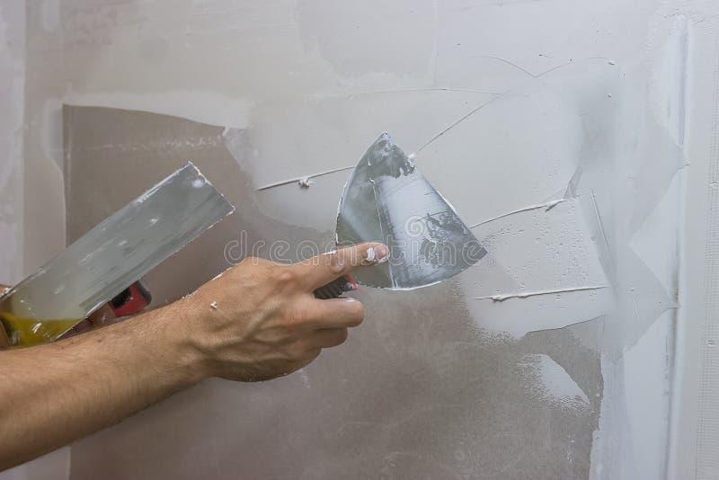 供以人员有涂灰泥墙壁2的修平刀的手 免版税库存图片