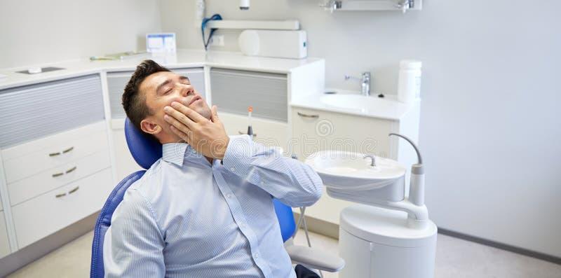 供以人员有牙痛和坐牙齿椅子 免版税库存图片