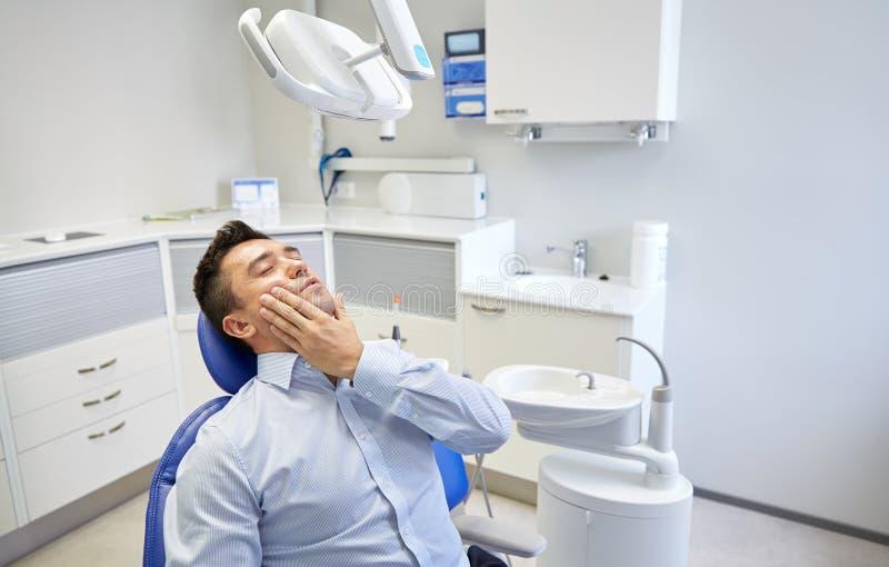 供以人员有牙痛和坐牙齿椅子 库存图片