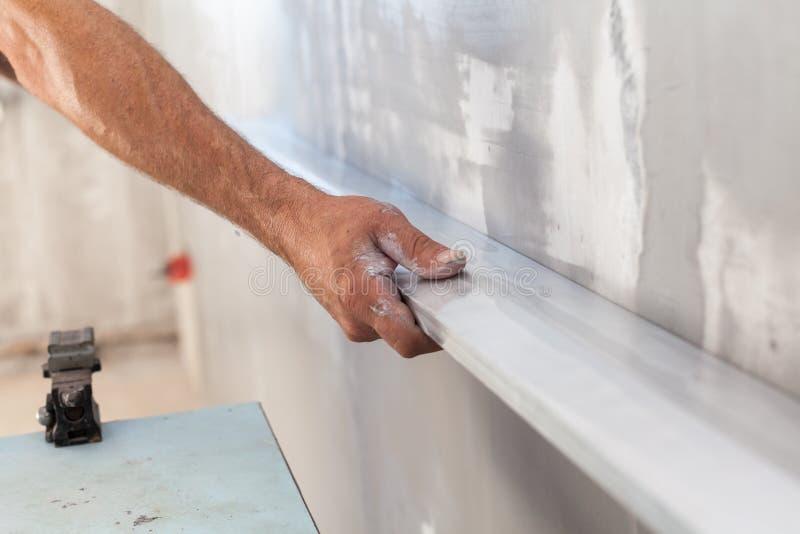 供以人员涂灰泥墙壁使用浮动规则检查扁平 免版税库存照片