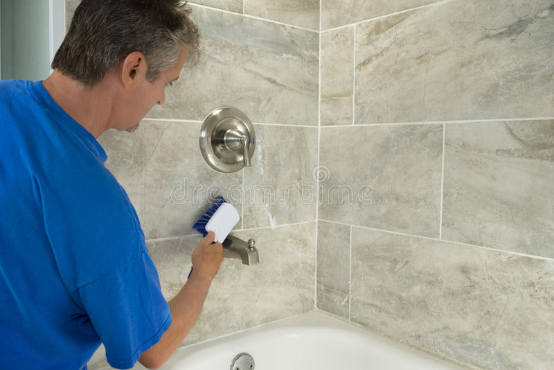 供以人员清洁浴缸瓦片,并且装置与刷子 库存图片