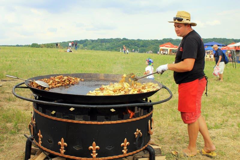 供以人员烹调在巨大的格栅室外平底锅的酥脆土豆, Pirogov 库存图片