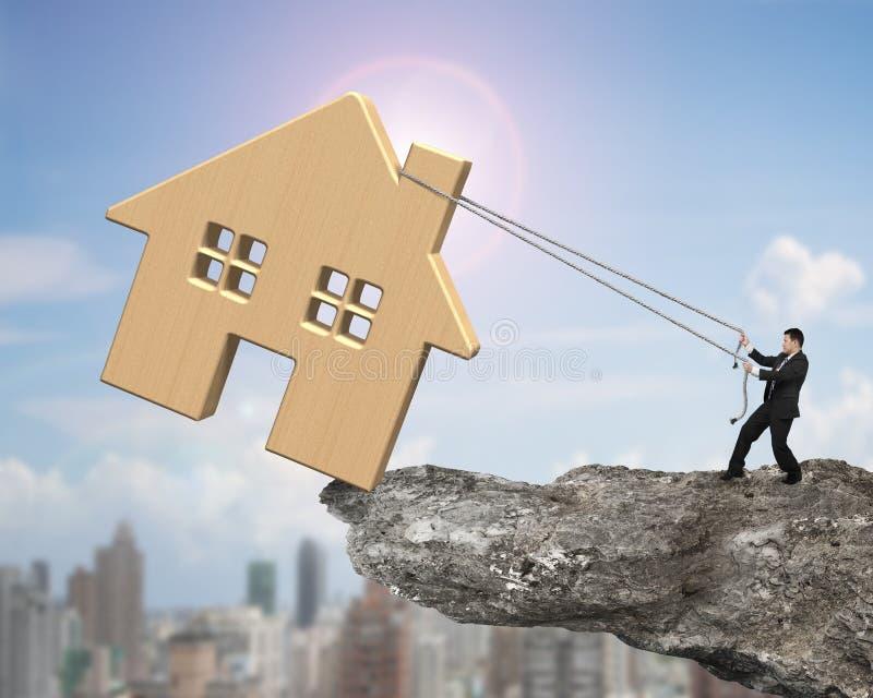 供以人员牵索移动峭壁边缘的木房子 免版税库存图片
