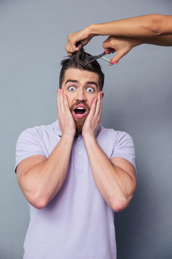 供以人员看吓唬,当剪他的头发时的女性手 免版税库存图片