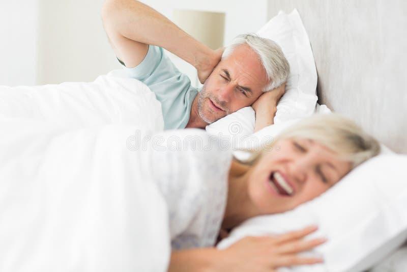 供以人员覆盖物耳朵,当呼喊在床上时的妇女 库存图片
