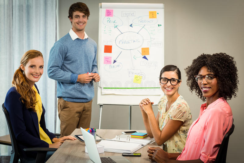 供以人员谈论在白板的流程图与工友 免版税库存图片
