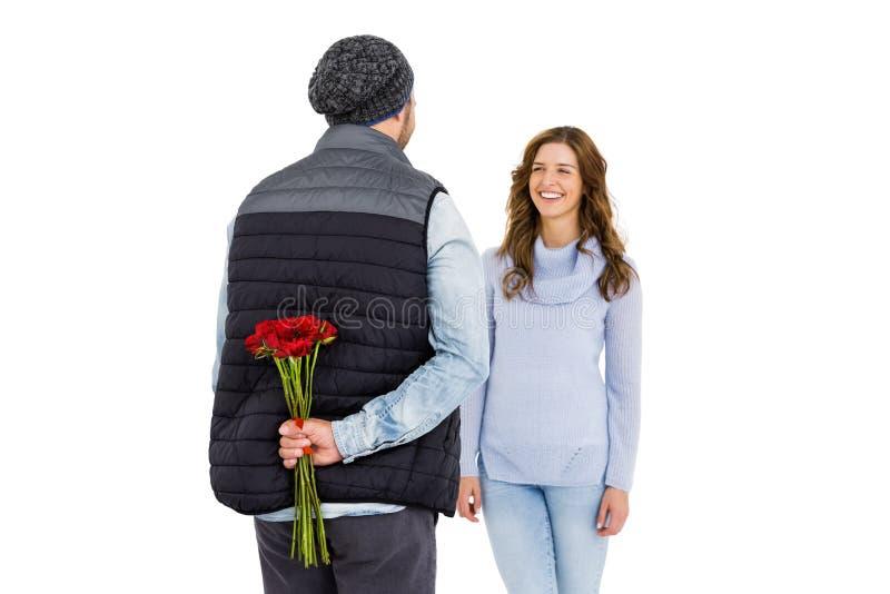 供以人员躲藏起来从在他的后的一朵玫瑰他的妇女 免版税图库摄影