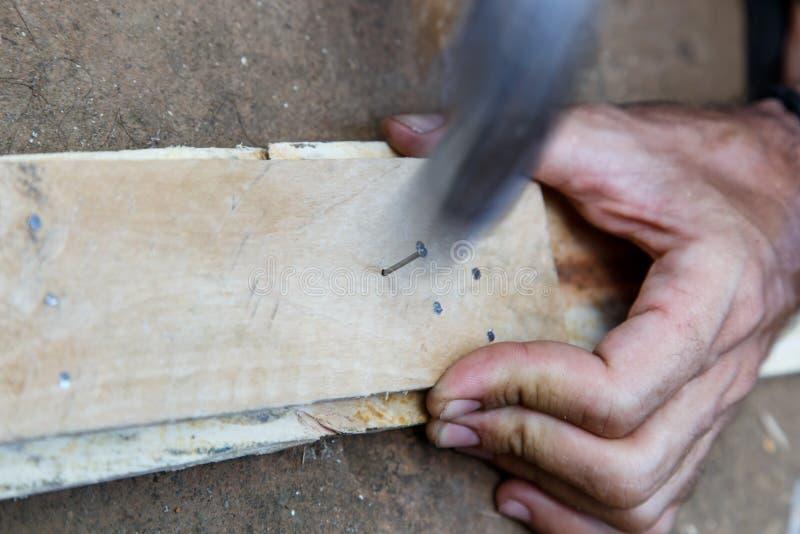 供以人员运转在与锤子的木头的手 库存照片