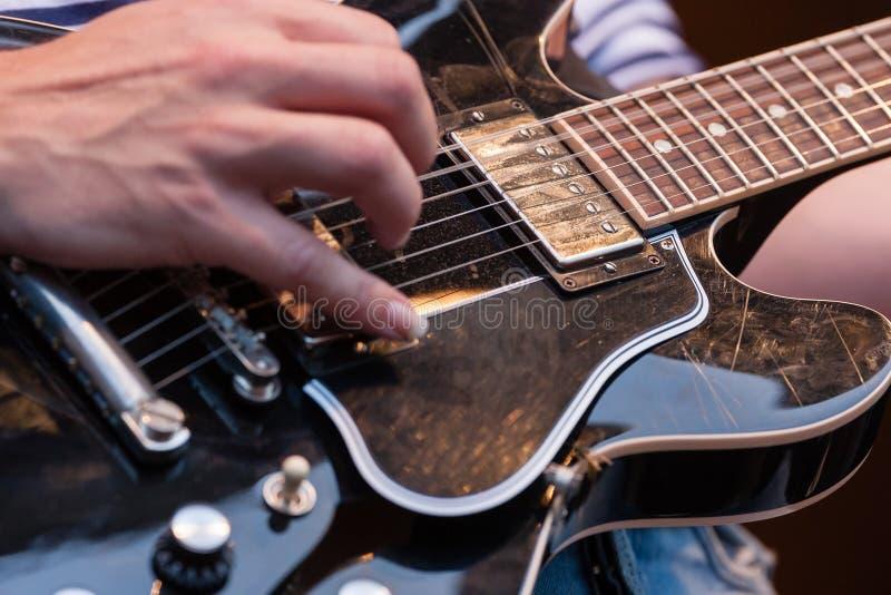 供以人员采在一把电吉他的串 库存照片