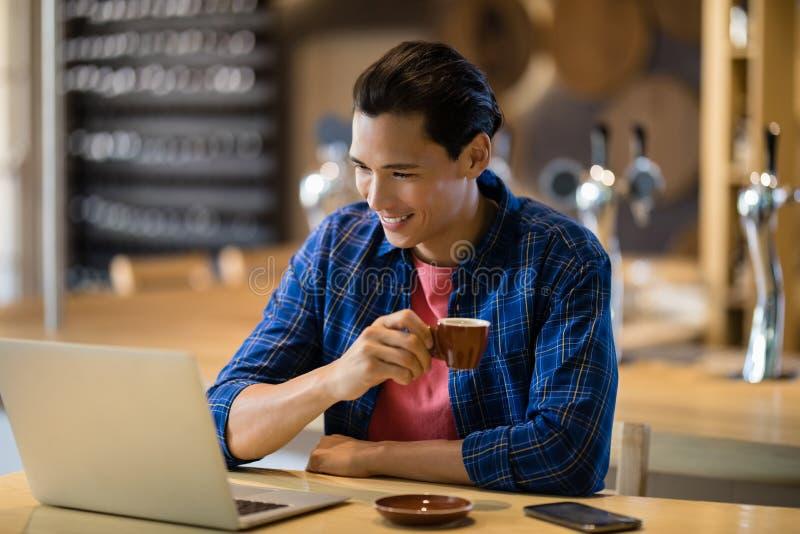 供以人员食用咖啡,当使用膝上型计算机在餐馆时 图库摄影