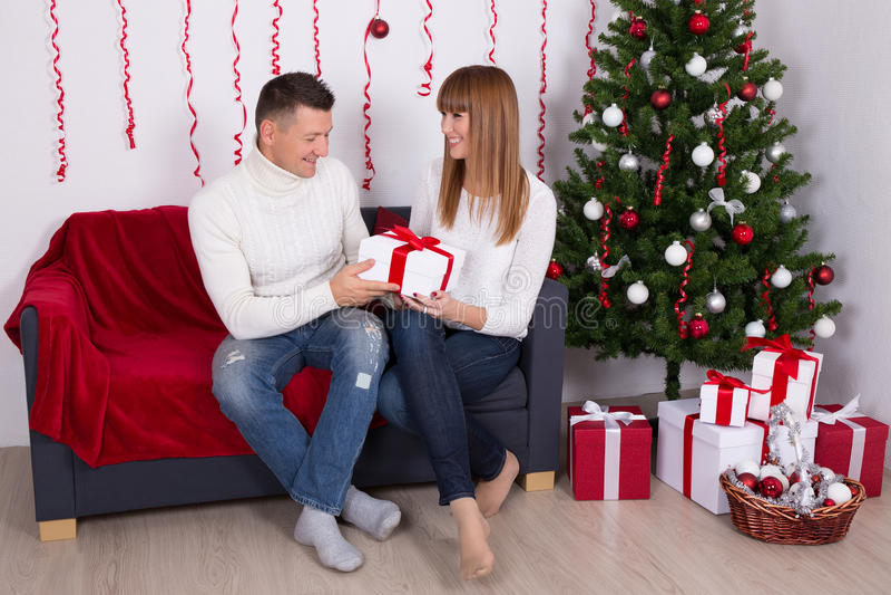 供以人员给圣诞节礼物他的妻子或女朋友得体的 免版税库存图片