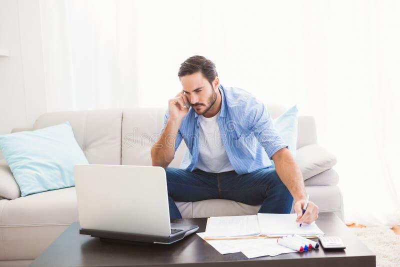 供以人员付他的与膝上型计算机的帐单,当谈话在电话时 免版税库存照片