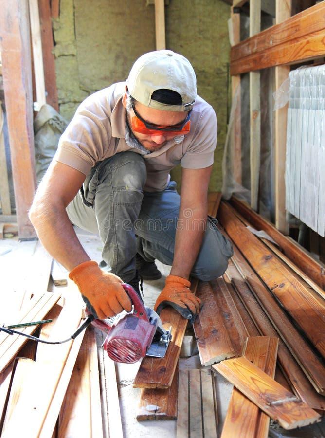 供以人员建立一房子和workimg与木头 免版税库存图片