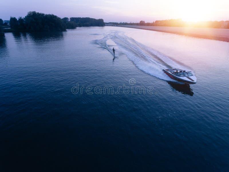 供以人员skiiing在小船后的湖的水 库存图片