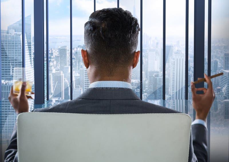 供以座位的商人抽烟的雪茄和喝,当看蓝色窗口时 库存图片