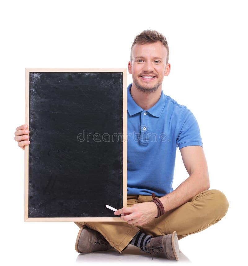 供以座位的年轻人供以人员与白垩和黑板 库存照片