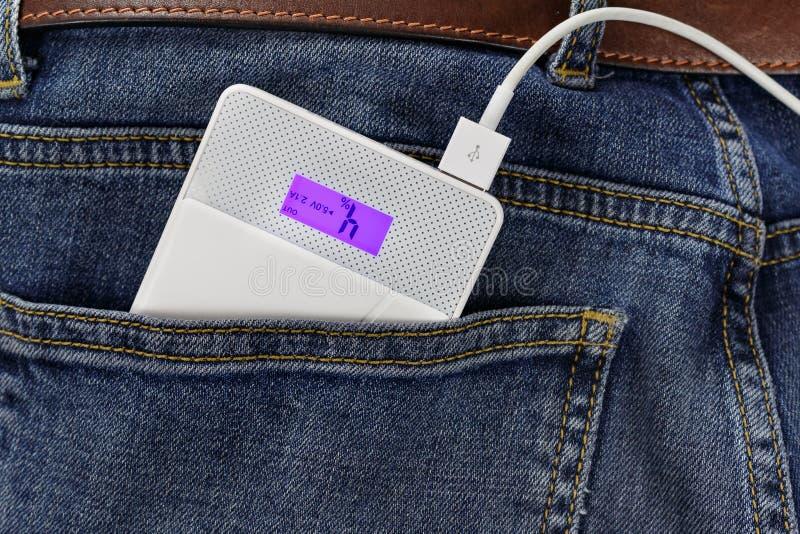 供给有连接USB缆绳的银行动力在牛仔裤特写镜头的后面口袋 免版税库存图片