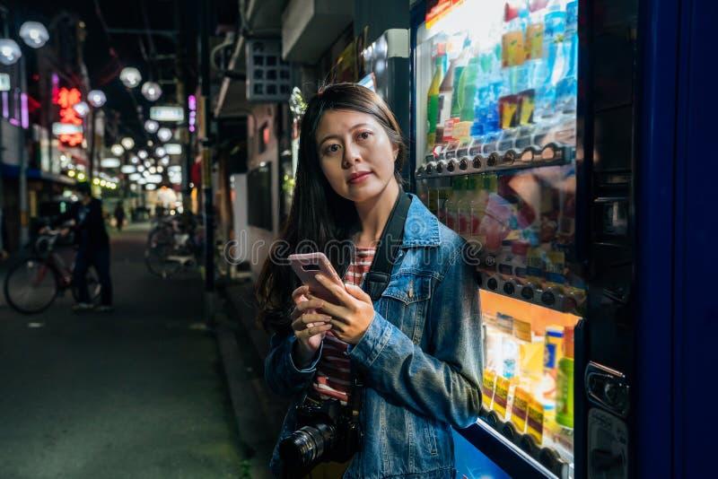 依靠日本贩卖机的日本妇女使用手机放松 年轻学生或女性游人有照相机短信的sms的 库存图片