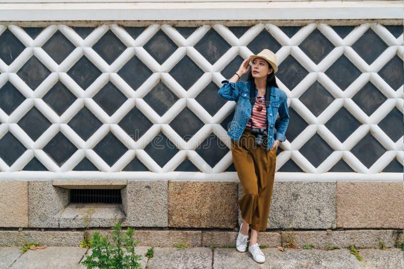 依靠白色净墙壁的年轻有吸引力的旅游佩带的草帽全长照片  典雅的亚洲旅客身分 免版税库存图片