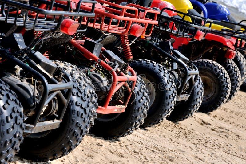 依顺序摩托车在海滩沙子 库存照片