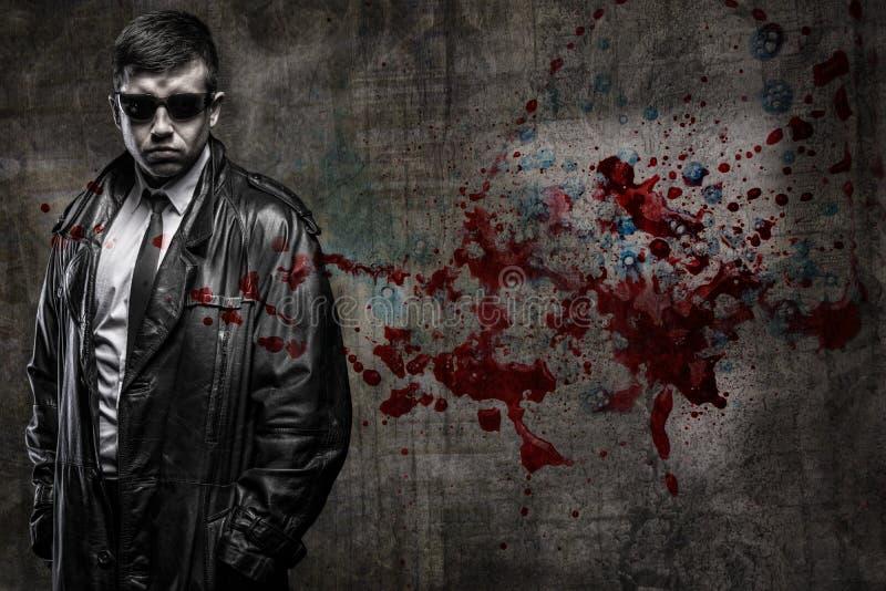 血淋淋的墙壁背景的侦探人 库存照片