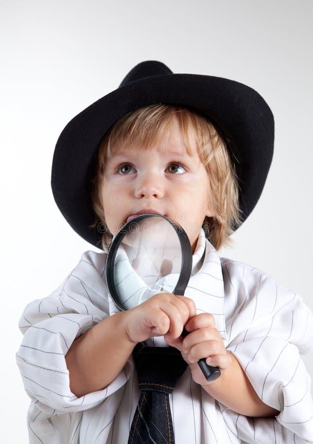 侦探玻璃扩大化的年轻人 库存照片