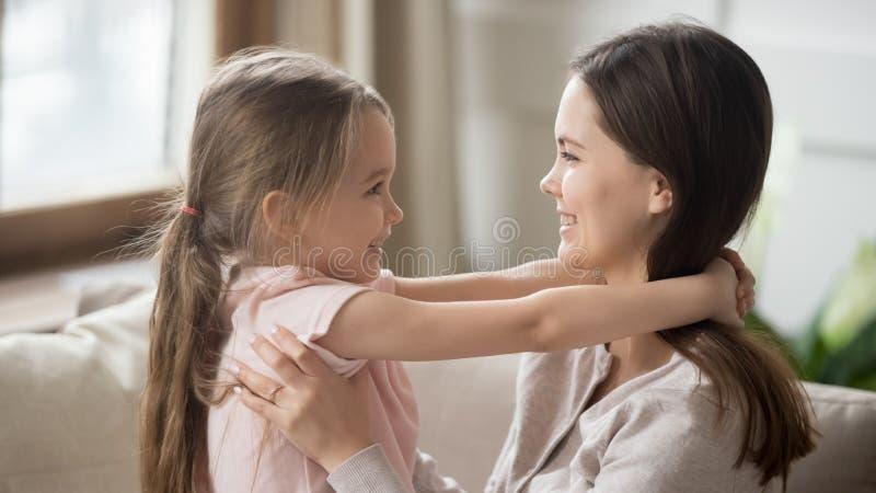 侧视图可爱的拥抱女儿和爱恋的母亲显示爱 免版税库存照片